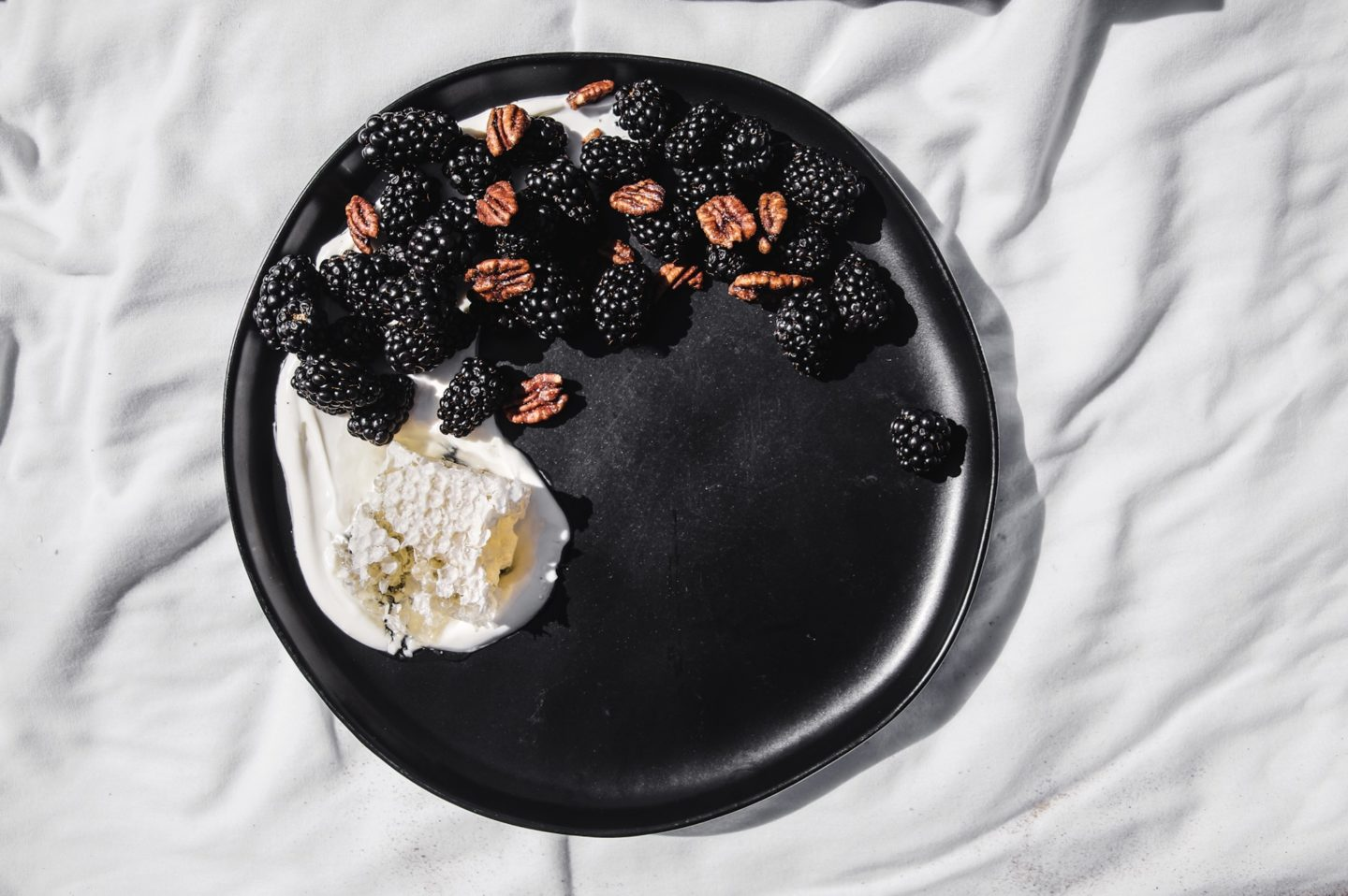 creme fraiche smeared on a plate with honeycomb blackberries and candied pecans.