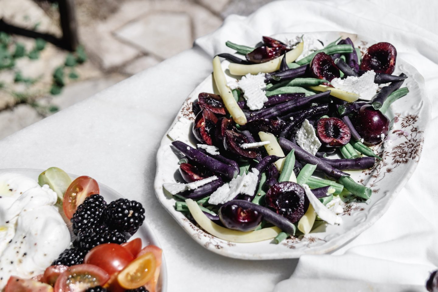 Multi-color snap bean summer salad with sweet dark cherries.