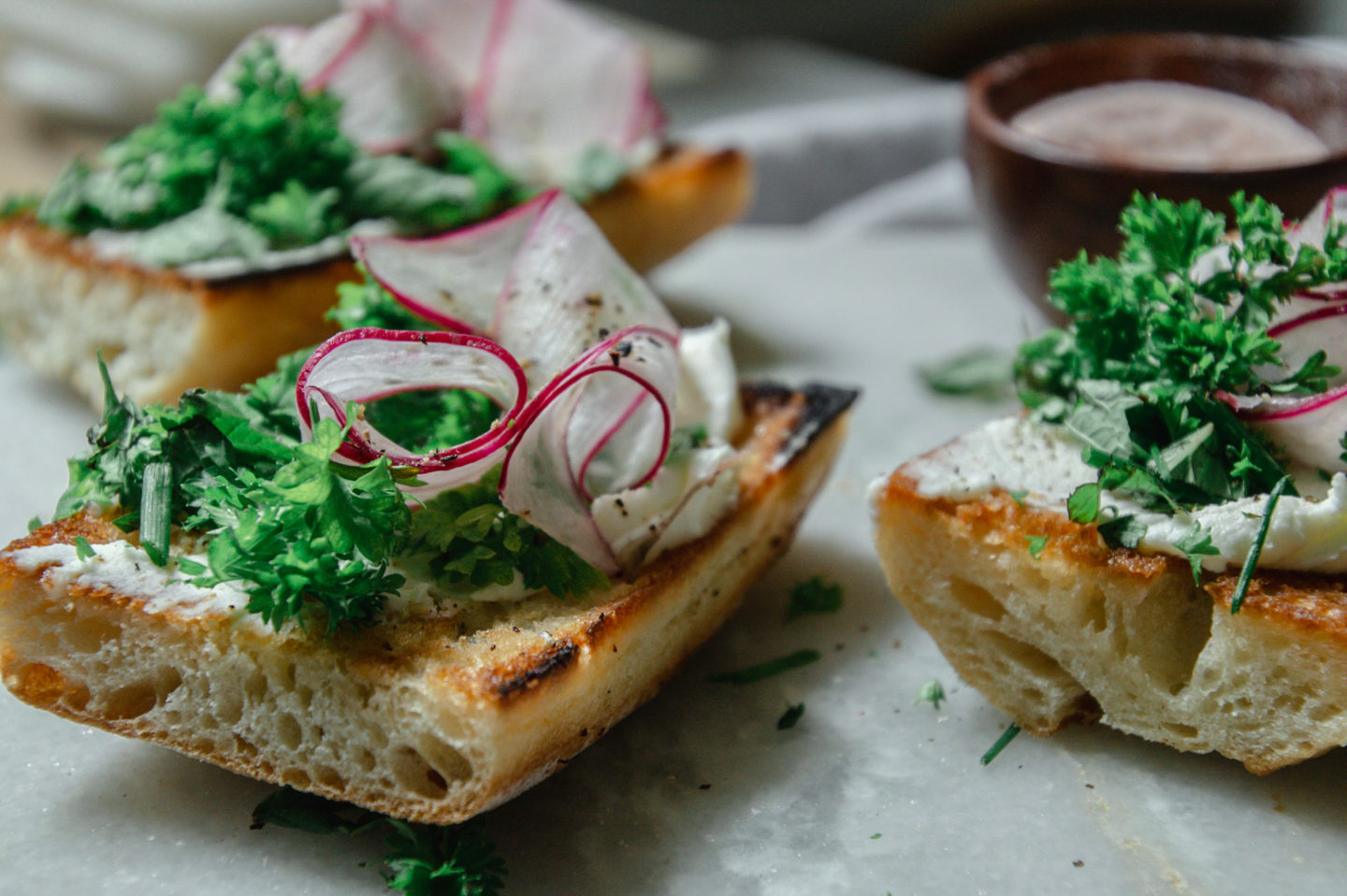 thin slices of curled radish top these toasts