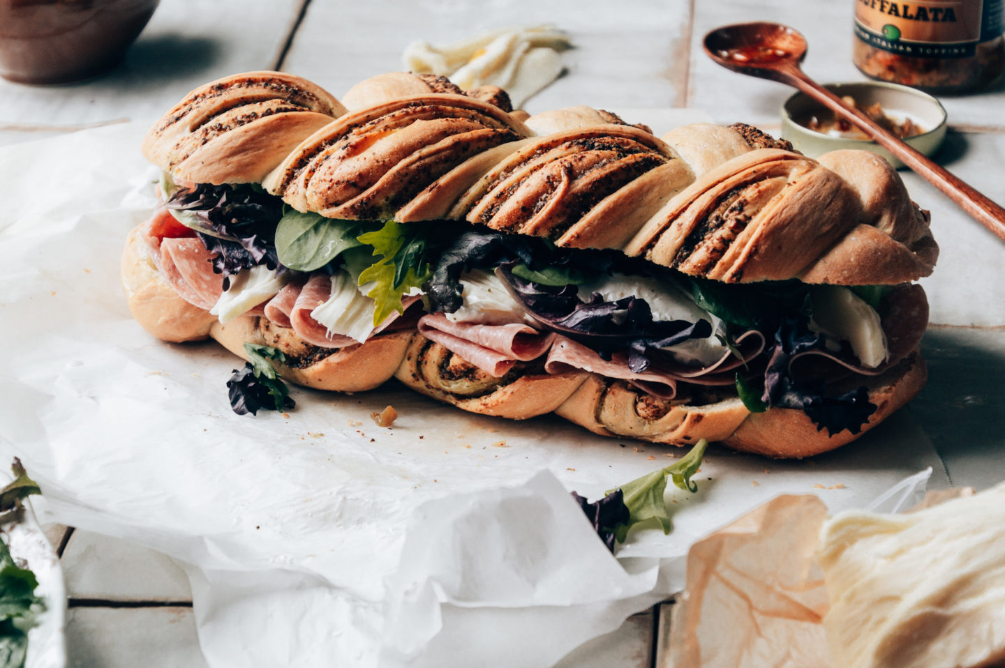 braided pesto bread adds a tasty twist on the classic Muffaletta and it's an impressive showstopper to serve at picnics and BBQ's