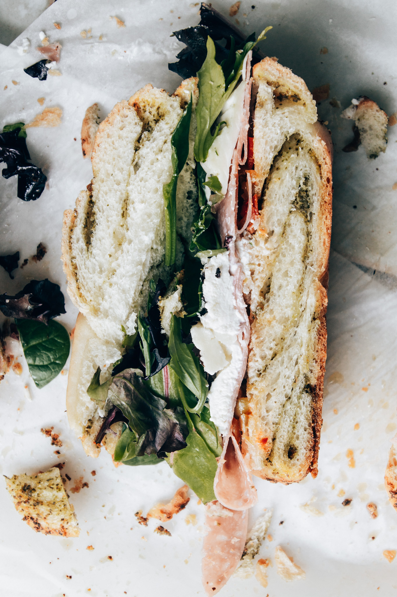 this muffuletta sandwich gets its unique look from swirls of pesto baked right into the bread