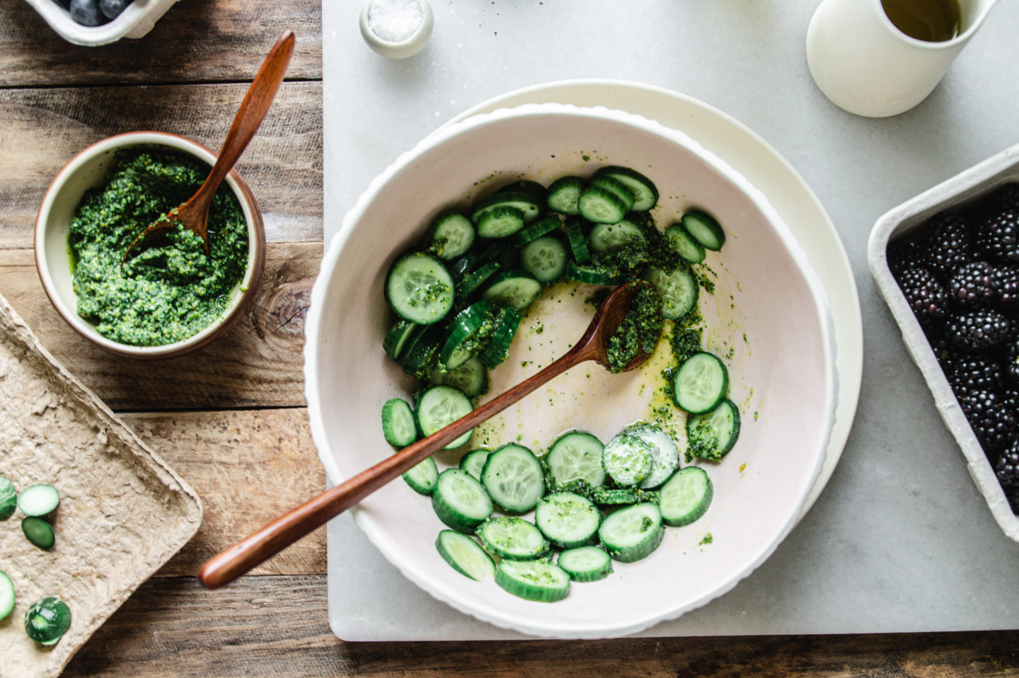 mix the sliced cucumbers, pesto, olive oil, and vinegar in a bowl to make the green goddess dressing