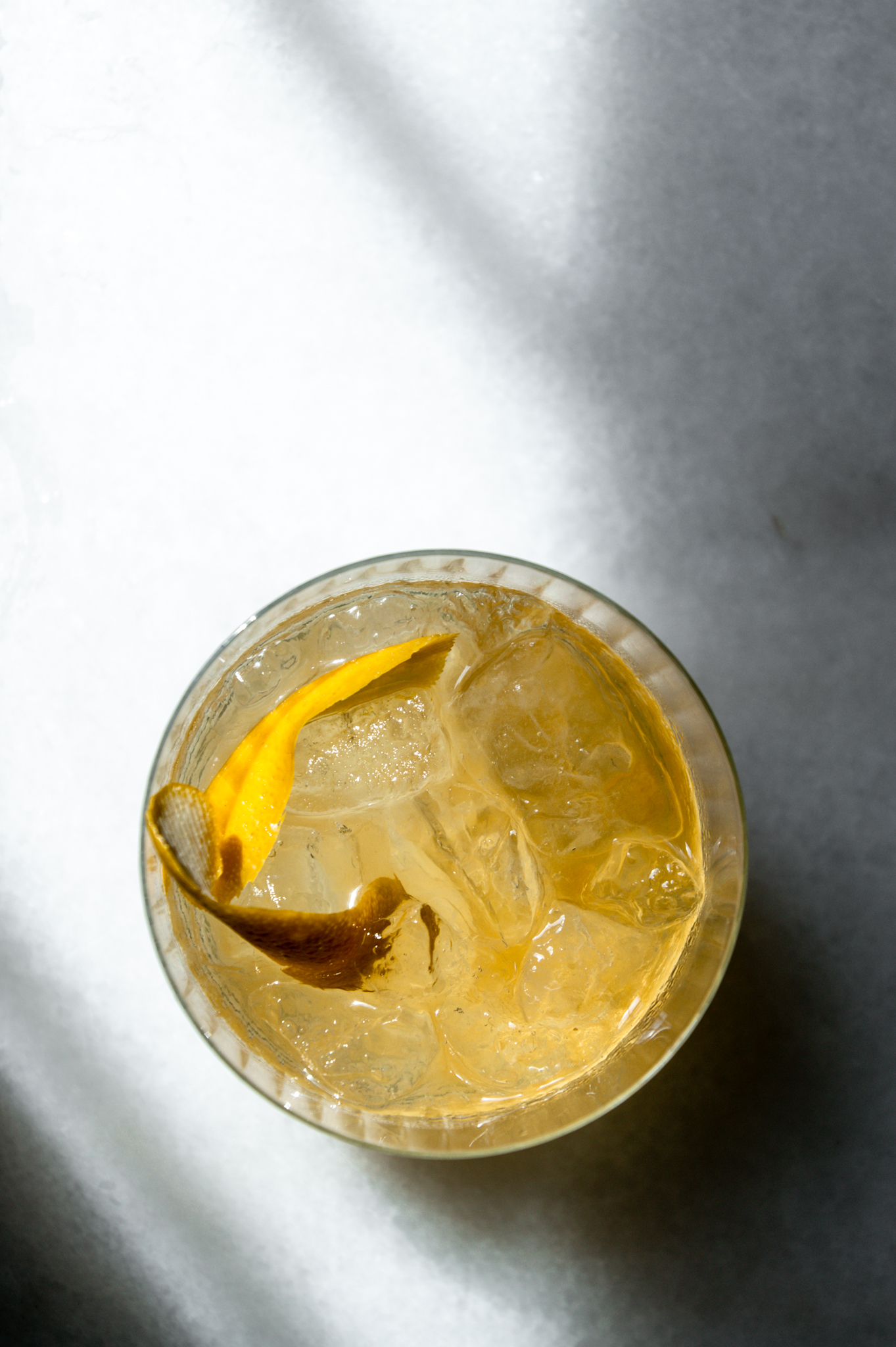 Elderflower whiskey sour on the rocks with a twist, made with St. Germain and homemade lemon syrup